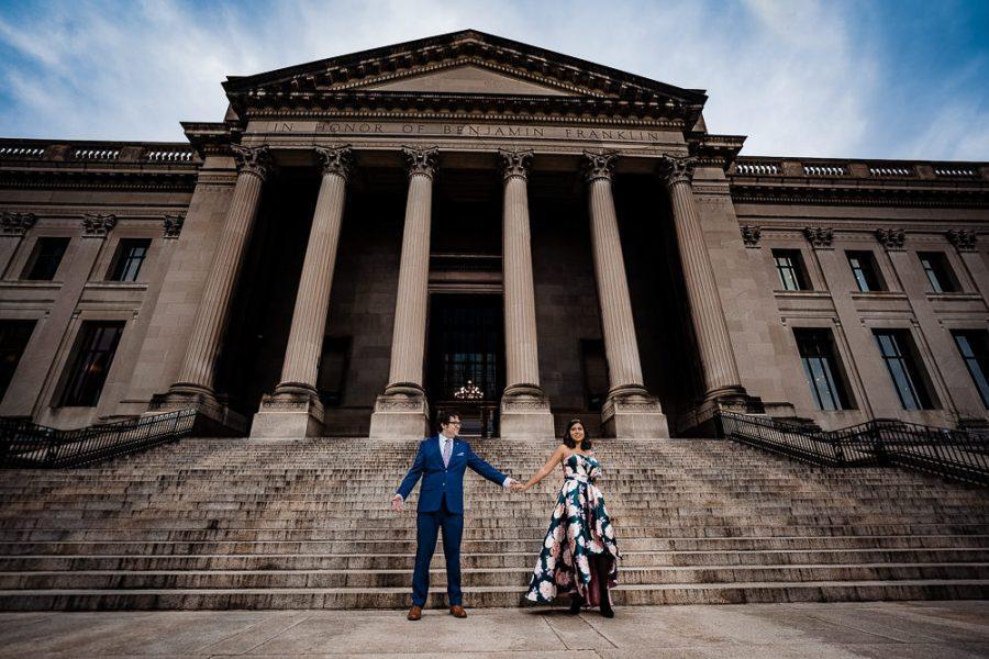 couple holding hands in front of philadelphia art museum