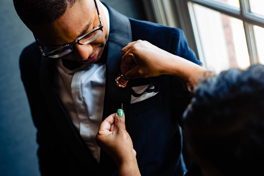 groom getting help with lapel pin