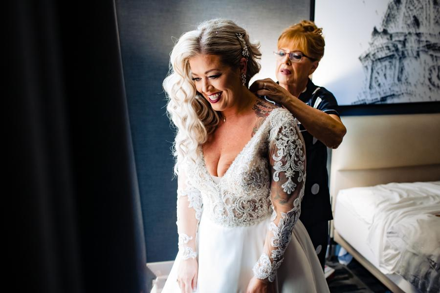 mom helping daughter into wedding dress
