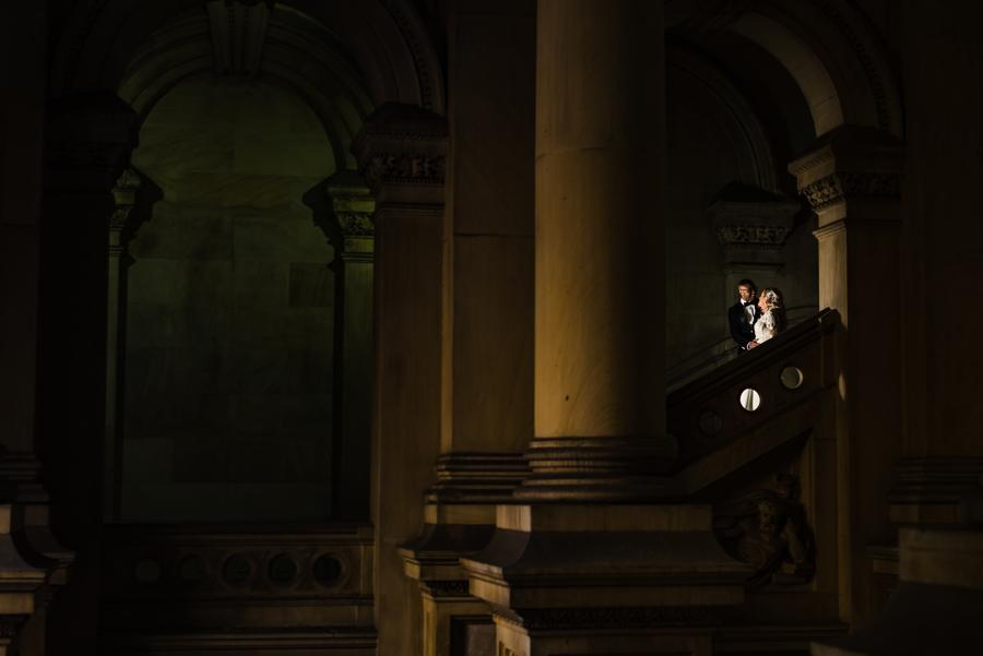 bride and groom posed on grand staircase