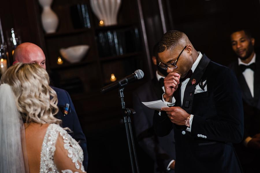 groom reading his vows to his bride