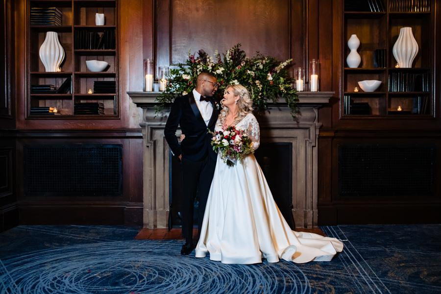bride and groom pose in front of library fireplace