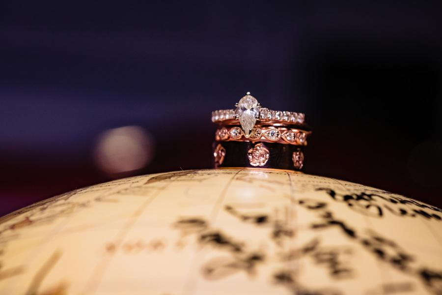 engagement and wedding rings on globe
