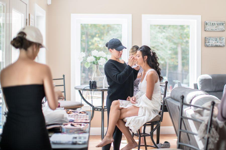 bride being made up by makeup artist