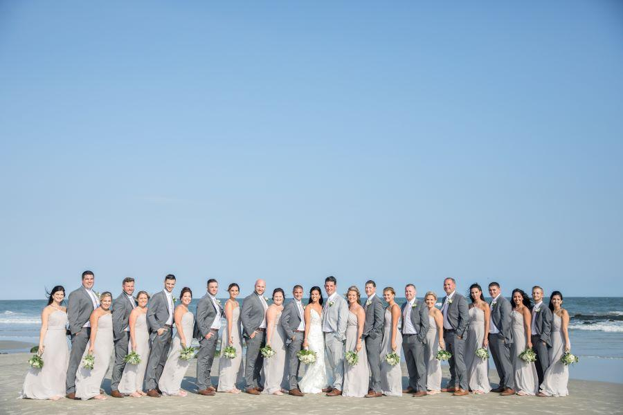 bridal party on beach in front of ocean