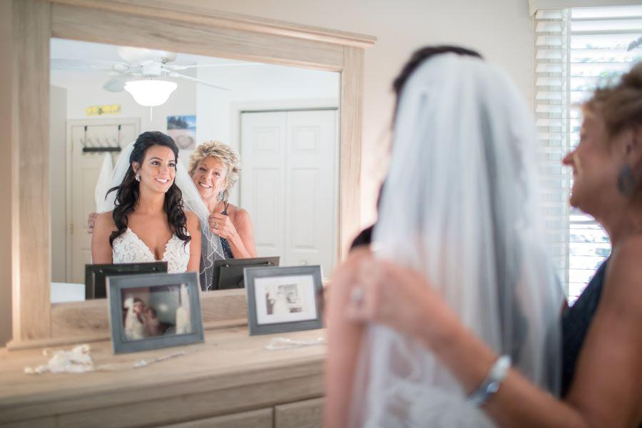 bride getting veil put on by mom