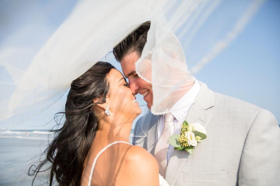 bride and groom enveloped by veil on beach