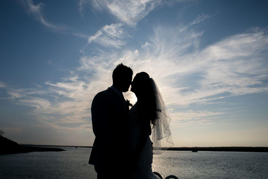 bride and groom embrace on beach at sunset