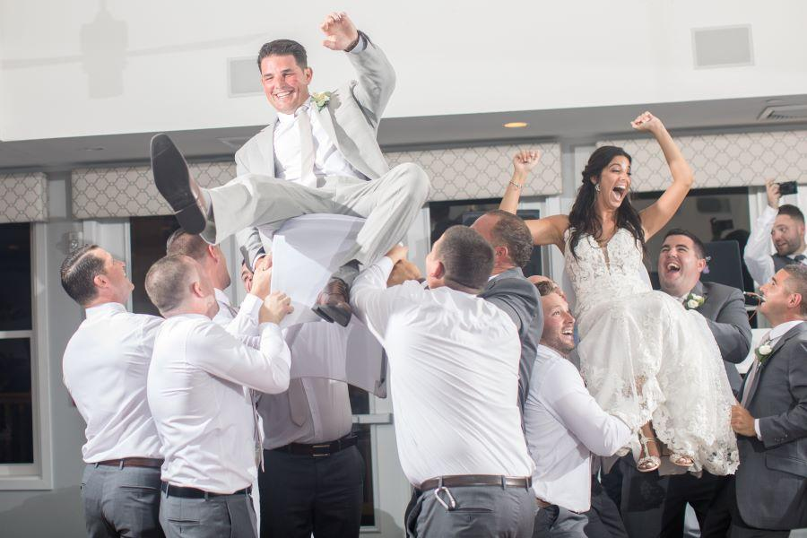 bride and groom hoisted up in chairs by male guests