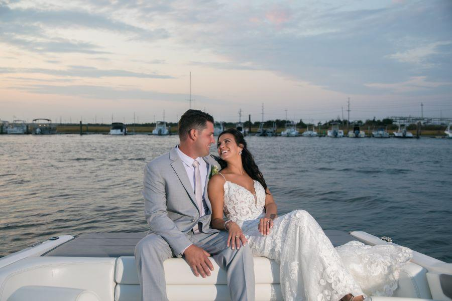 bride and groom on boat by bay