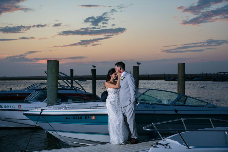 groom kisses bride's forehead at sunset