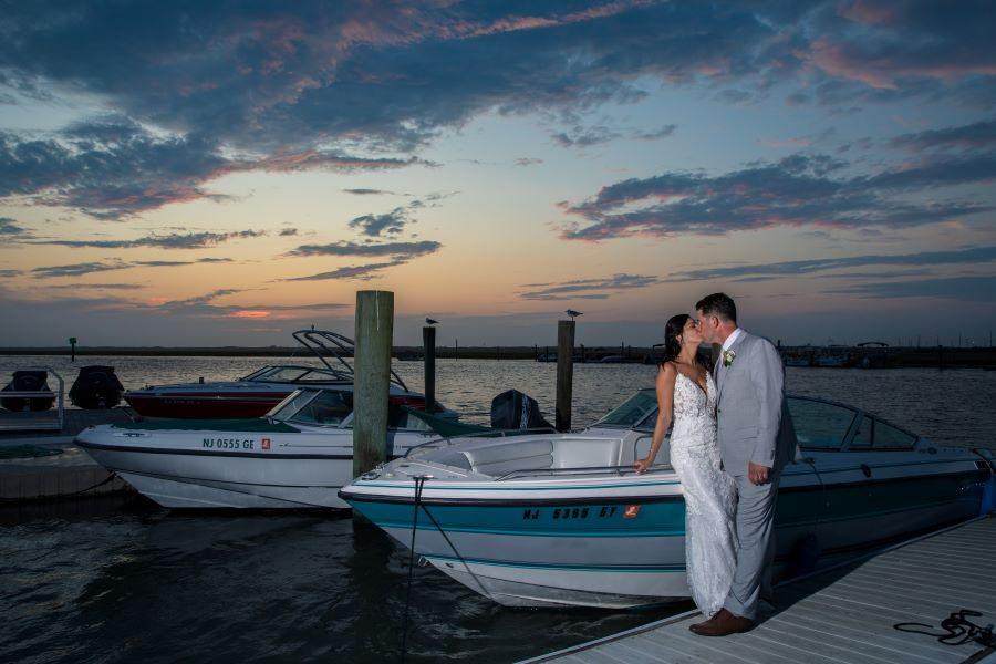 bride and groom kiss in front of boat at sunset