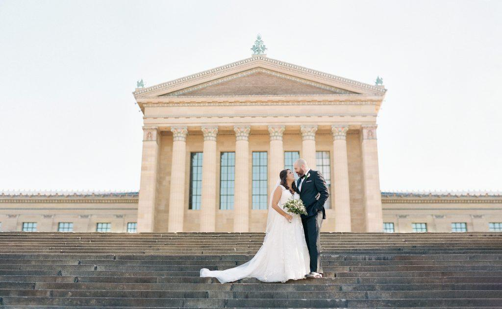 bride and groom pose in front of Philadlphia Museum of Art