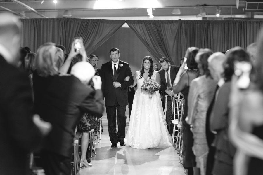bride walks down the aisle with father