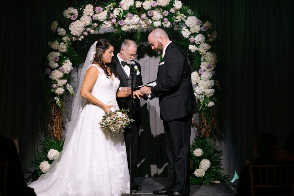 groom places wedding ring on bride