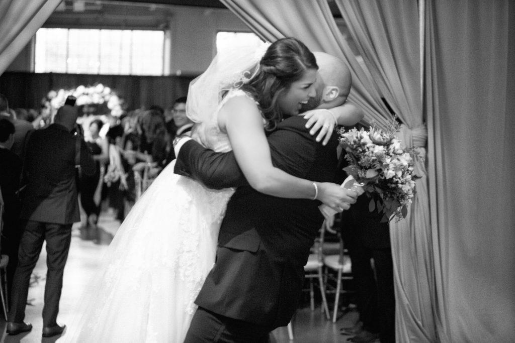 groom picks up his bride to hug