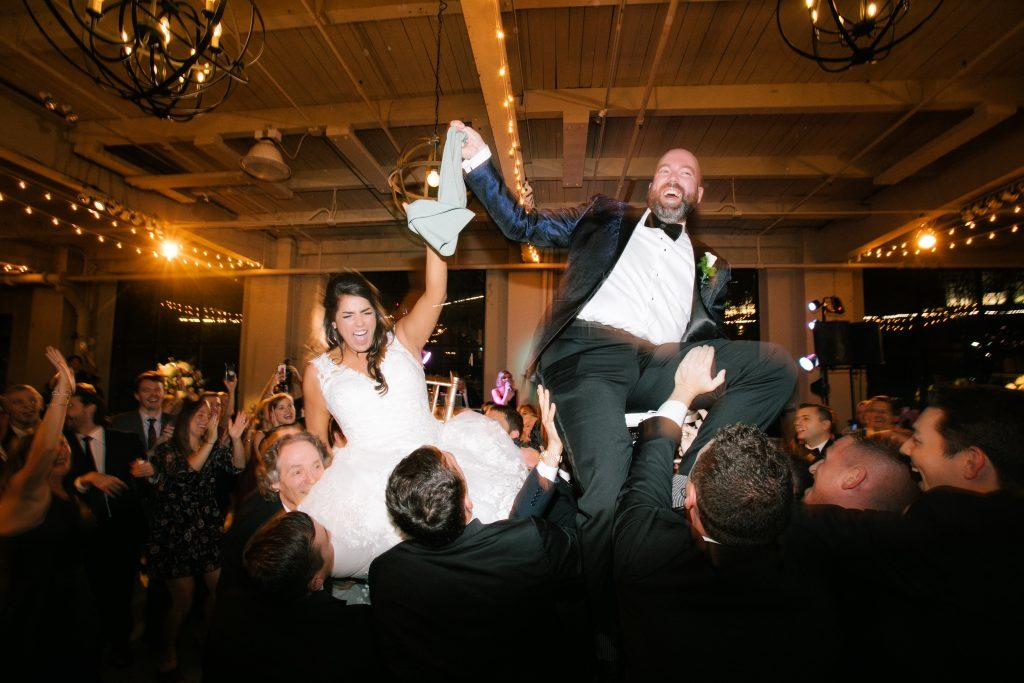 bride and groom lifted into chairs on dance floor