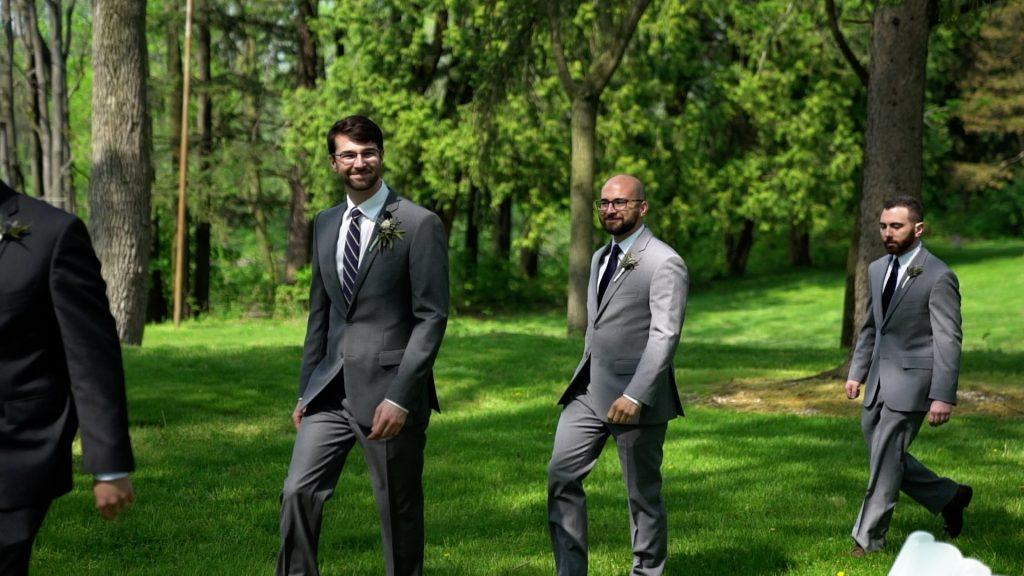 groom and groomsmen walk down aisle
