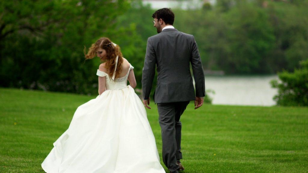 bride and groom walk on lawn at outdoor estate
