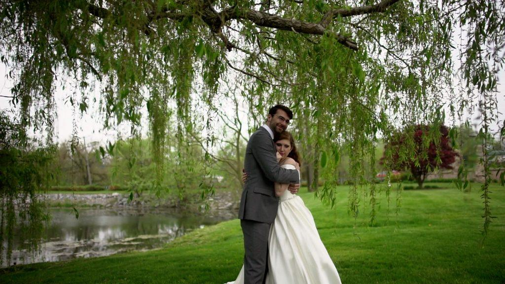 bride and groom embrace on lawn at Willow Springs Estates