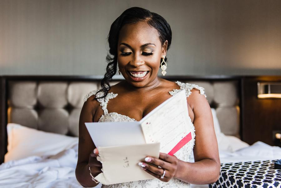 smiling bride reads card from groom