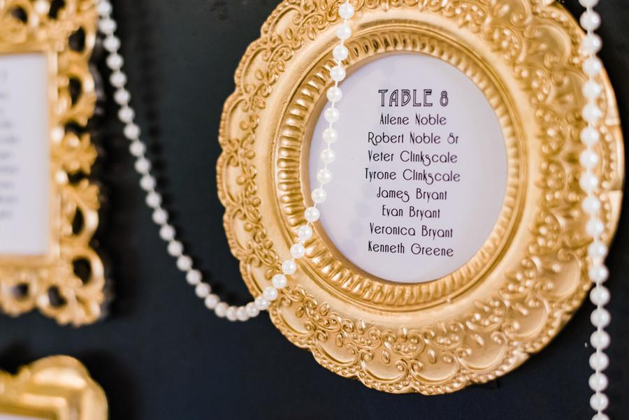 golden framed seat cards with pearls