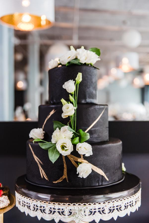 black frosted wedding cake with white roses