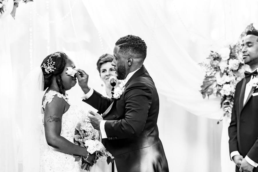 groom wipes away bride's tears at ceremony