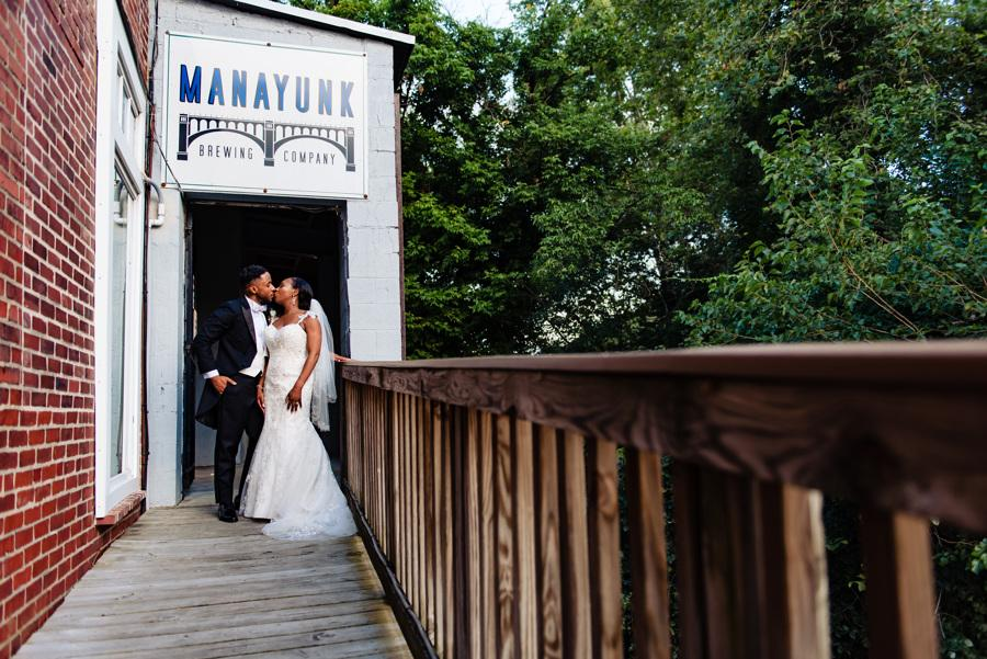 bride and groom kiss on deck of manayunk brewing company
