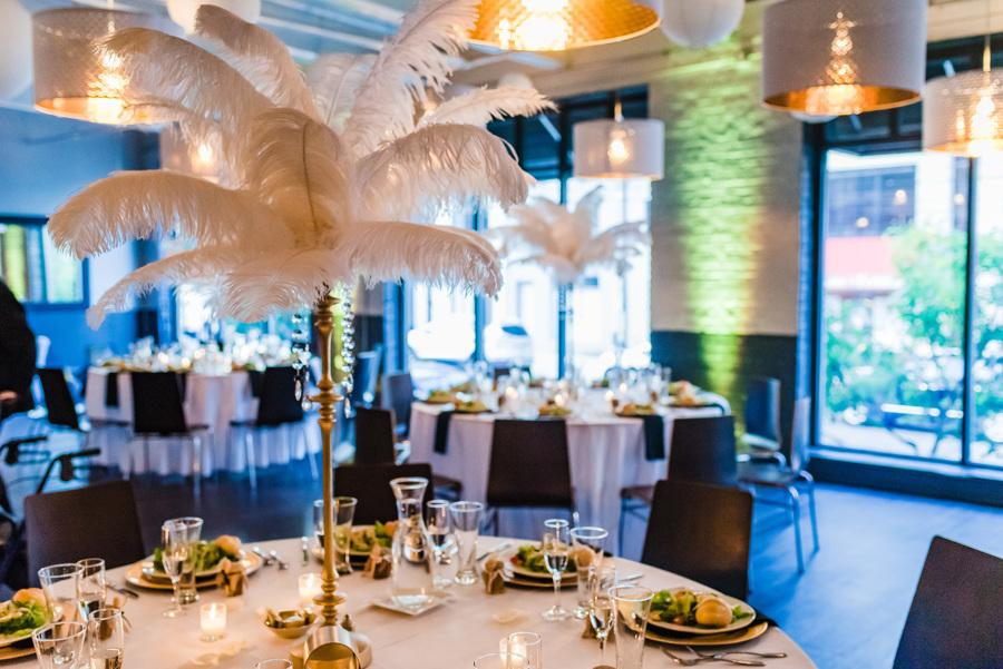 wedding reception table with white feather centerpiece