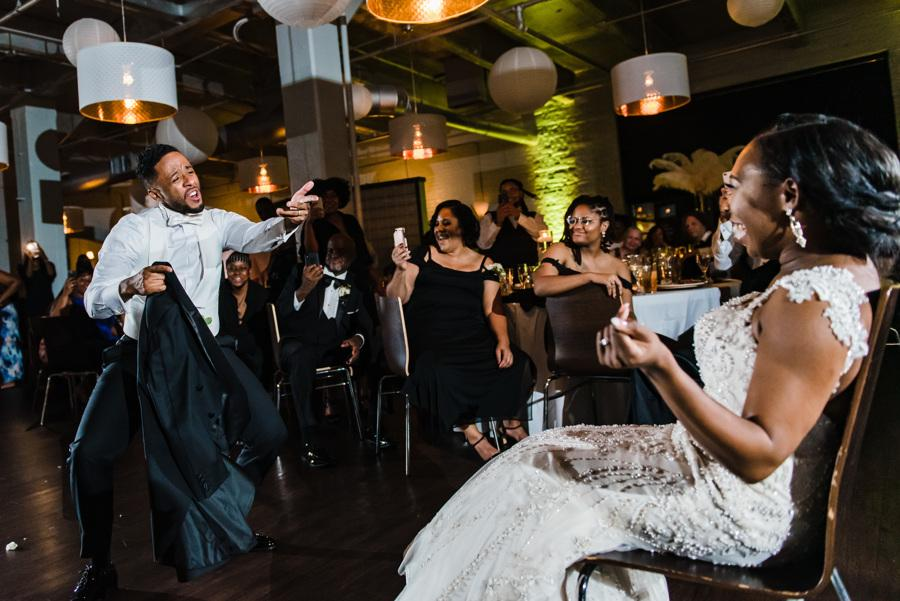 groom serenades bride at wedding reception