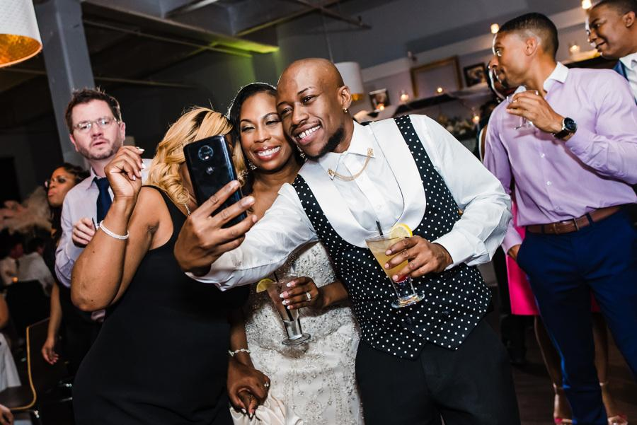 guests take wedding selfie
