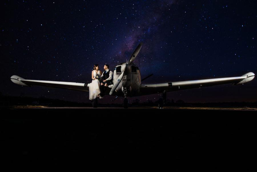 couple sit on wing of plane at night