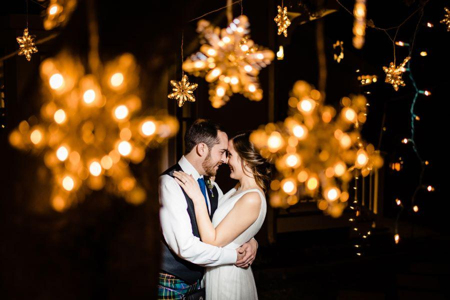 bride and groom among string lights