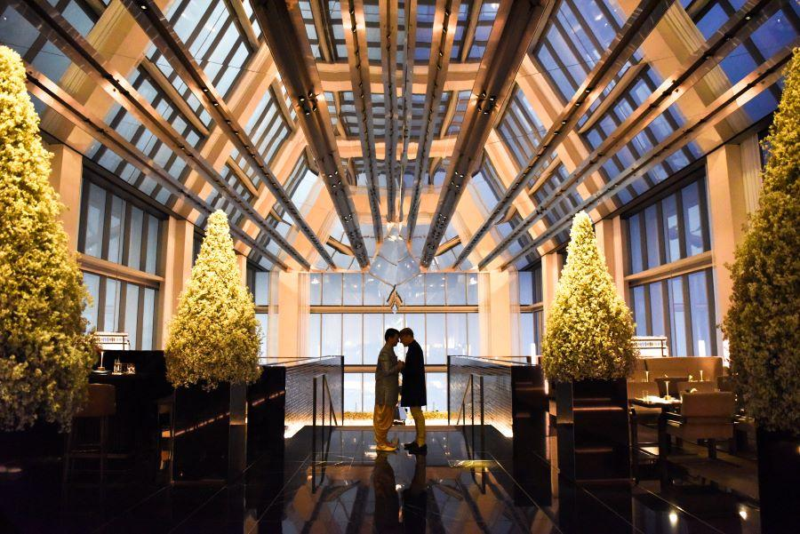 groom and groom stand in atrium