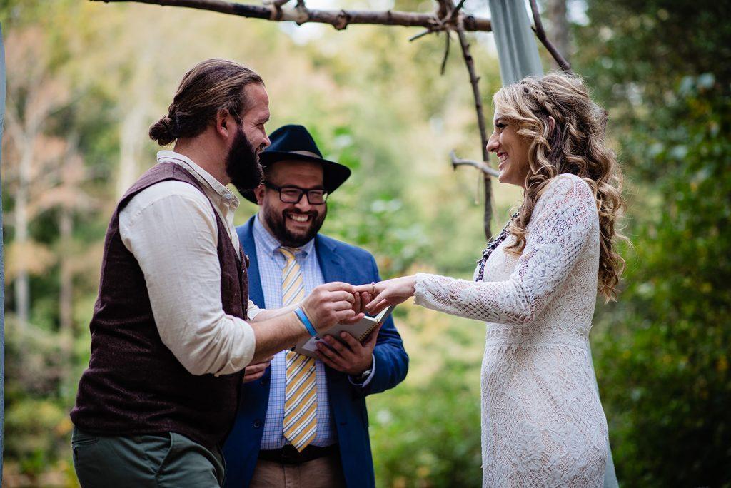 groom slips wedding ring on bride