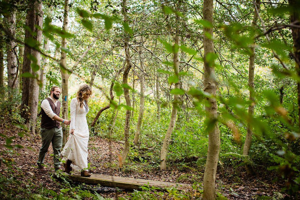 bride and groom walk and hold hands in forest