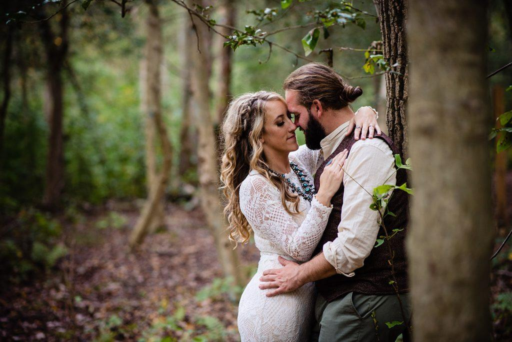 bride and groom embrace in woods