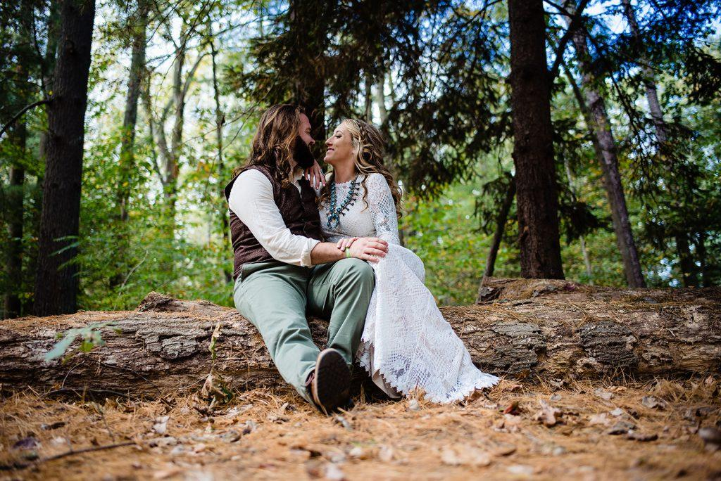 bride and groom sit in forest