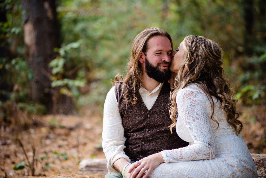 bride kisses groom sitting in woods