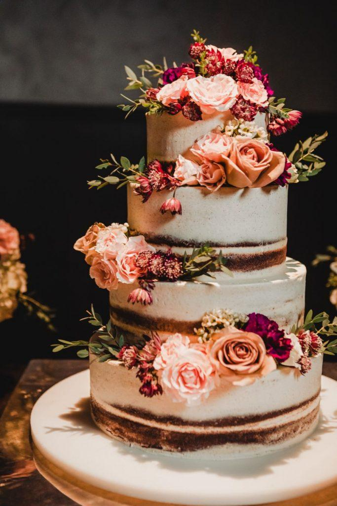 4-tiered naked wedding cake with pink roses