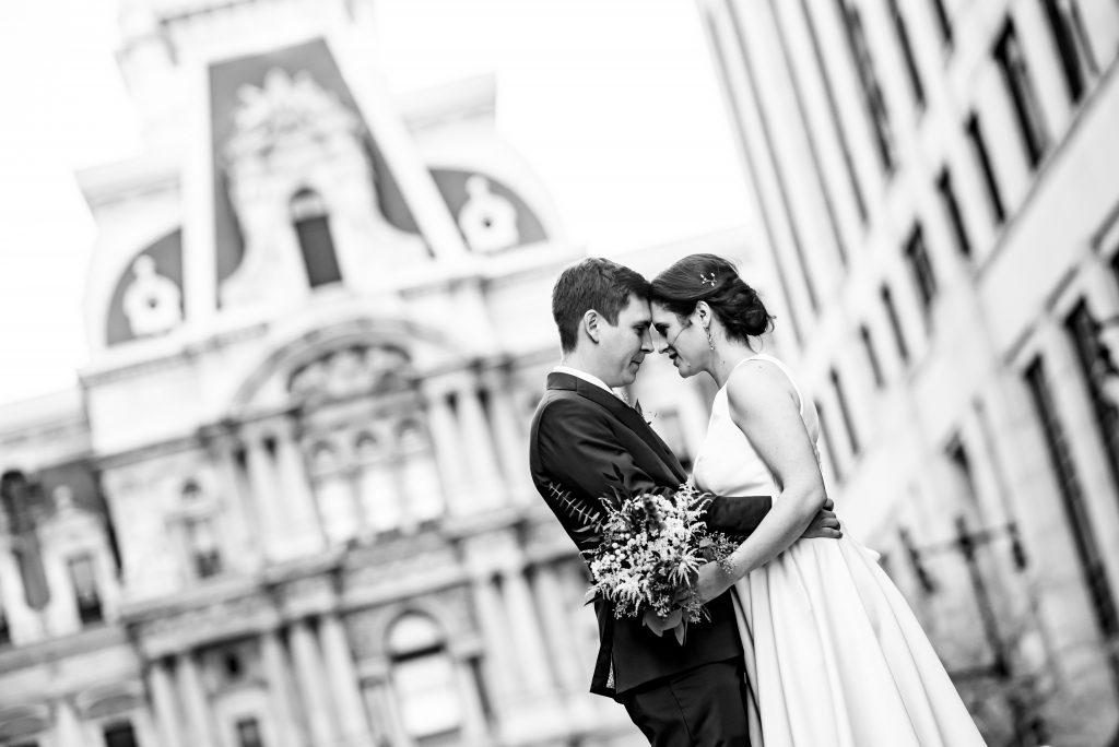bride and groom pose in front of Philly city hall