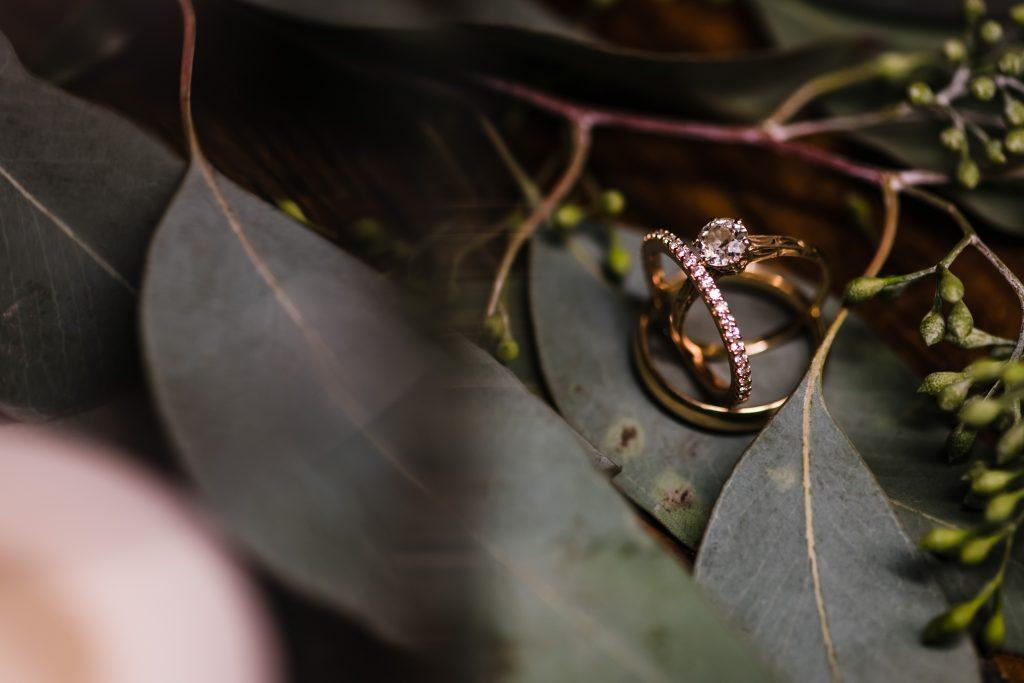 wedding band and engagement ring on leaves