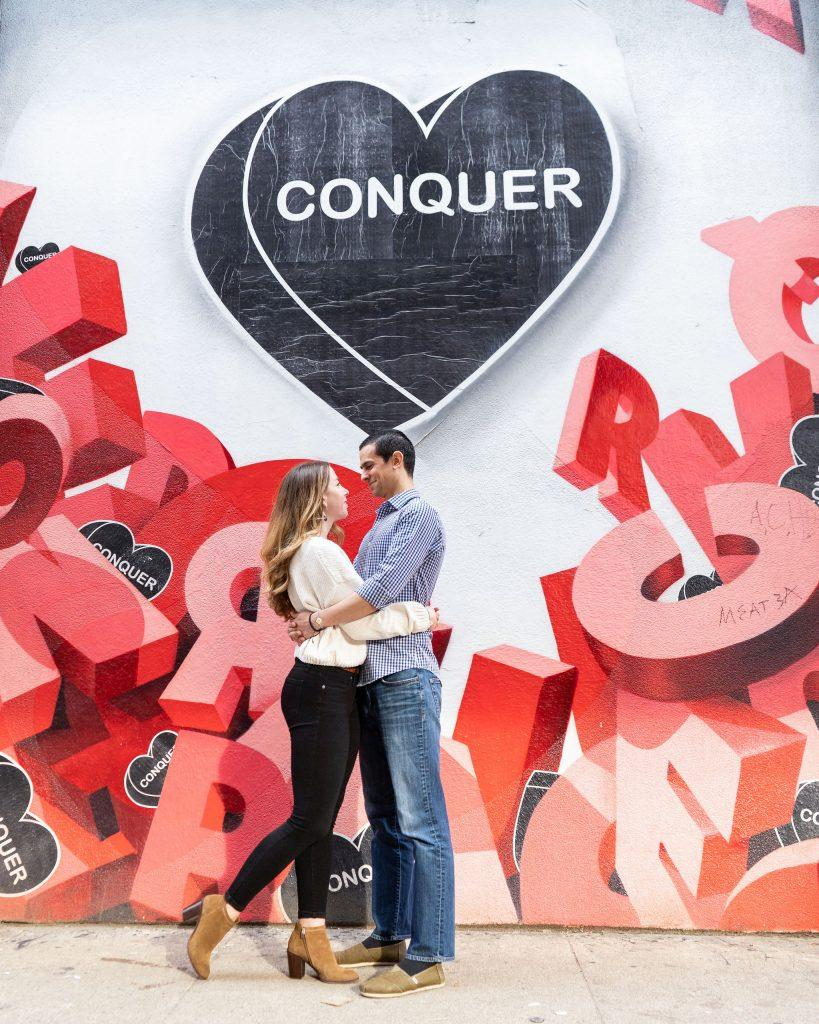 engaged couple hug in front of love mural