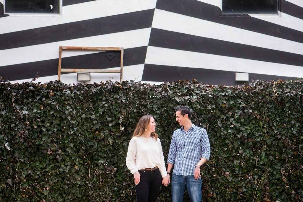 engaged couple hold hands in front of hedges and black and white mural