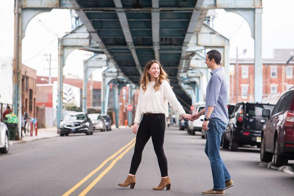 engaged couple holding hands while crossing street