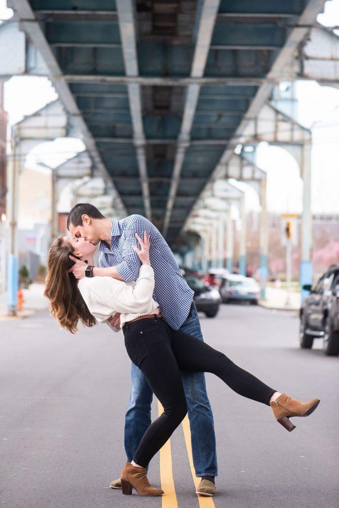 boyfriend romantically dips his girlfriend under train trestle