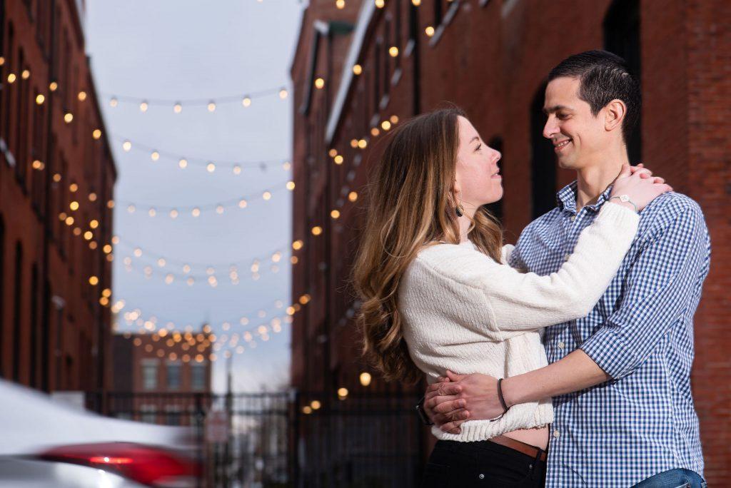 engaged couple hug under string lights in Fishtown