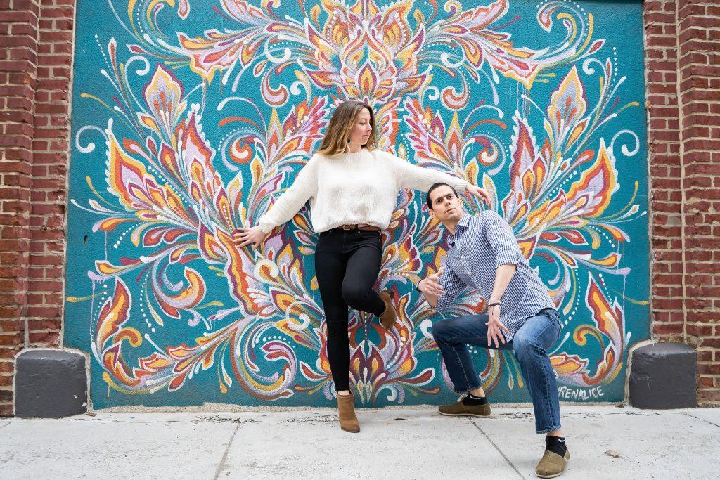 engaged couple posed in front of mural