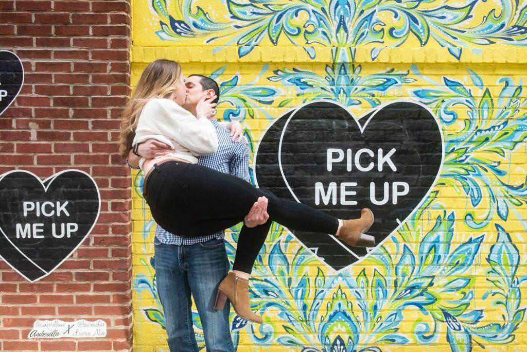 bride to be swept off her feet in front of mural